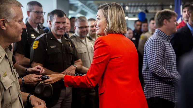 Iowa Gov. Kim Reynolds hands out pens to law enforcement officers after signing the Back the...