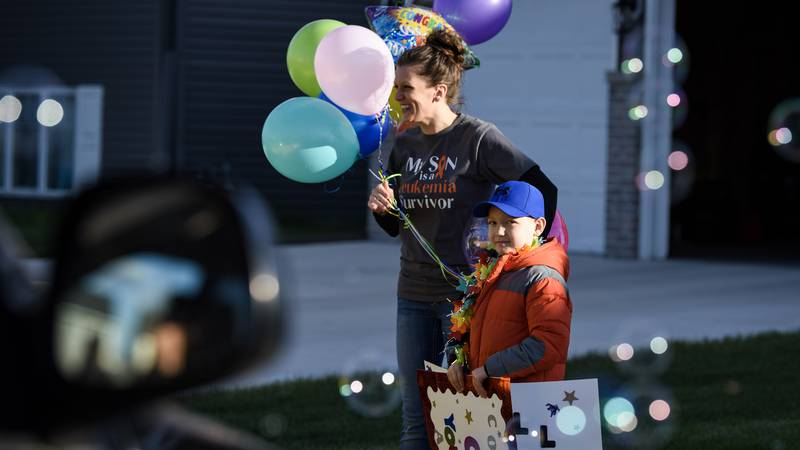 Seven-year-old Chay Simonson smiles as he looks at bubbles blownduring a parade celebrating...