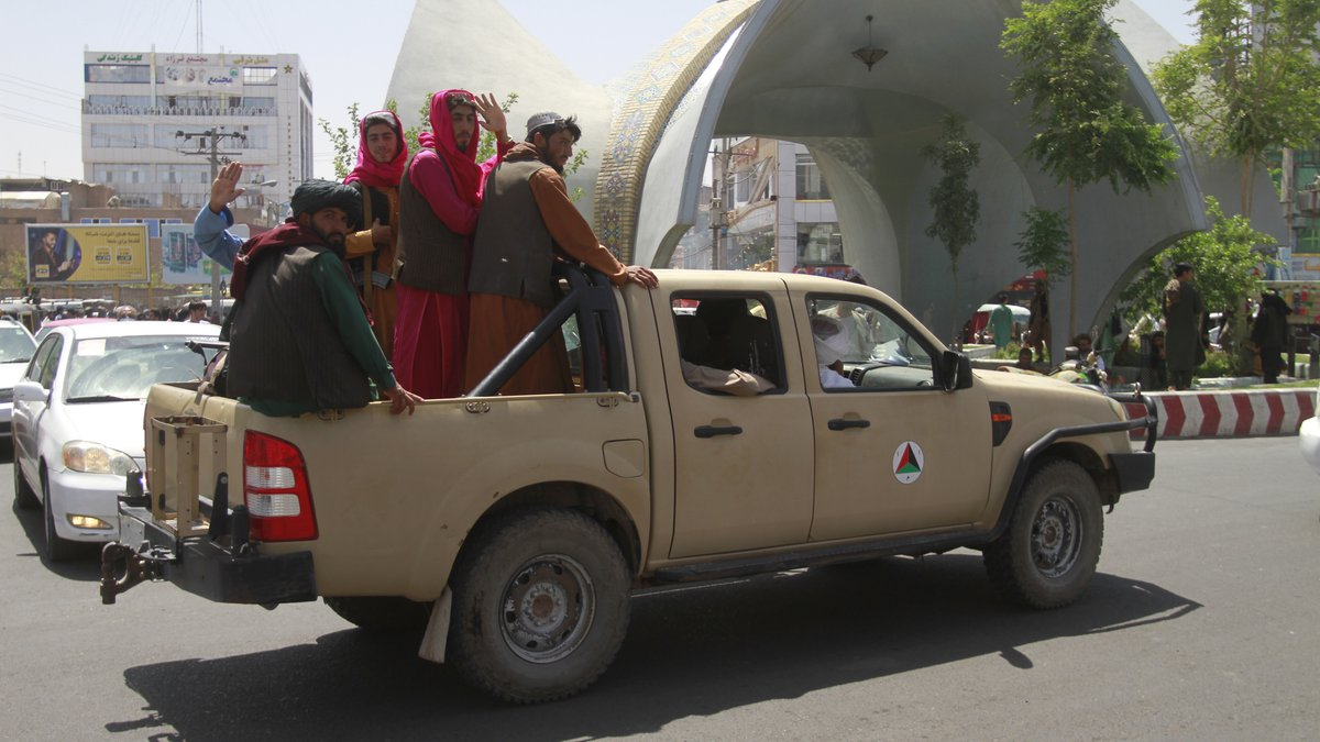 Taliban fighters pose on the back of a vehicle in the city of Herat, west of Kabul,...