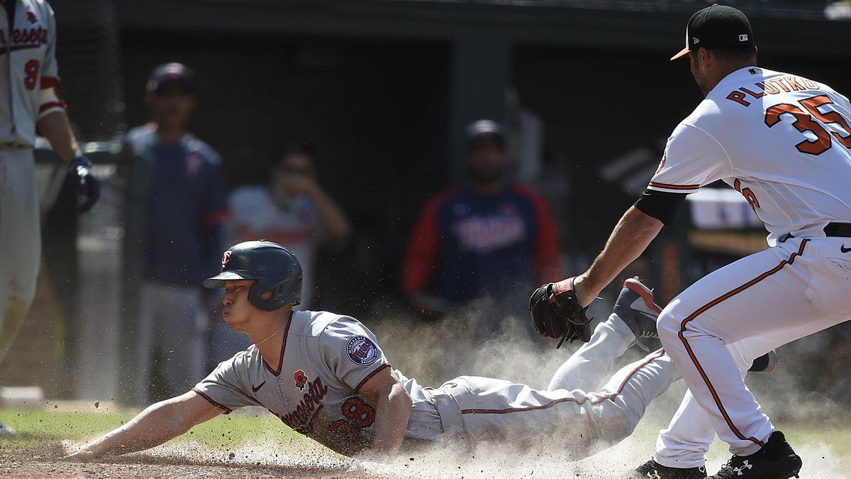 Minnesota Twins' Rob Refsnyder, left, slides across the plate as Baltimore Orioles pitcher Adam...