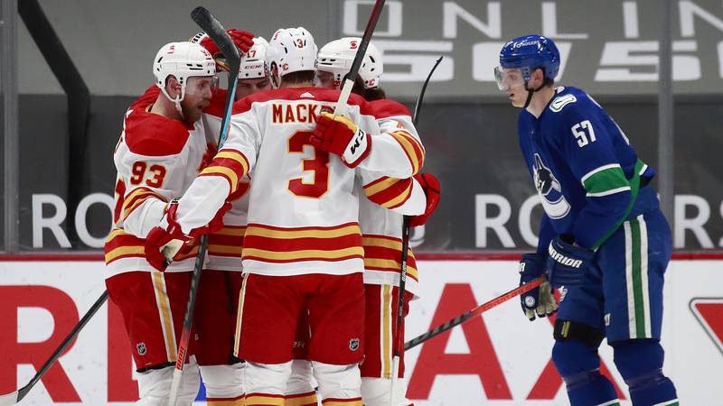 Connor Mackey (3) celebrates with his Calgary Flames teammates after assisting a Milan Lucic...