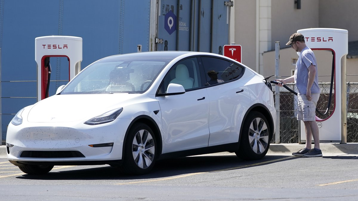 A Tesla owner charges his vehicle at a charging station in Topeka, Kan., Monday, April 5, 2021....