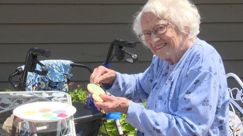 Resident of Carriage House Senior Living in Le Center, decorates a cookie, with children from...
