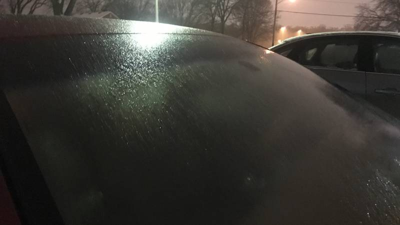Freezing drizzle causing a glaze of ice on car windshield.