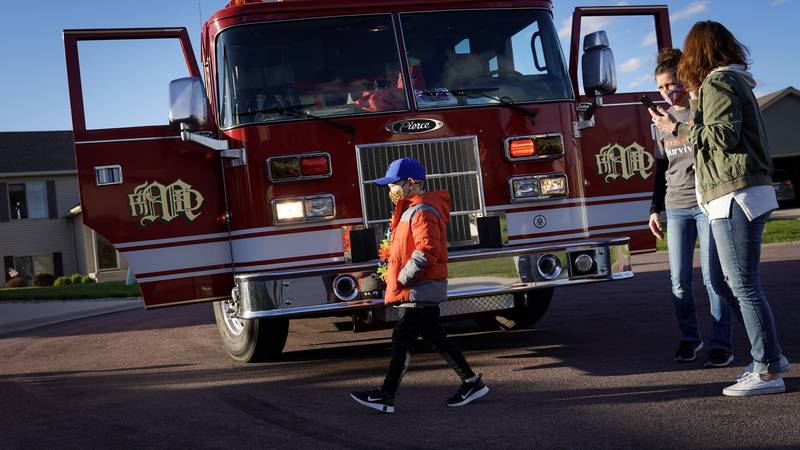 Seven-year-old Chay Simonson walks past a Mankato Fire Department fire truck he got to get...