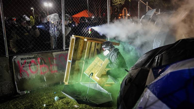 A demonstrator hides behind a makeshift barricade as they're shot with less-than-lethal marking...