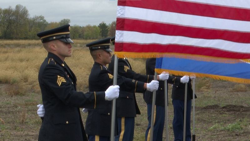 Military personnel hold flags during a groundbreaking ceremony Wednesday, Oct. 13, 2021, in...