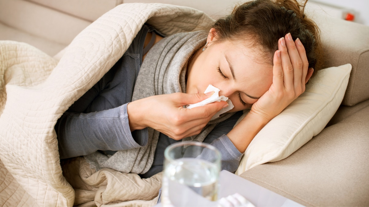 A woman lying in bed sick, blowing her nose.