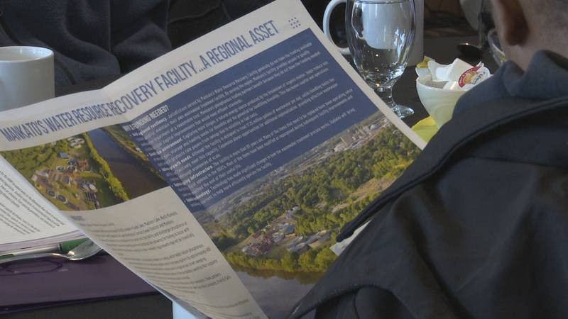Person reads pamphlet on Mankato Water Resource Recovery Facility project