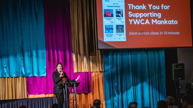 Sophie Hoiseth, YWCA Adult Programming Coordinator, talks silent auction, at Women of...